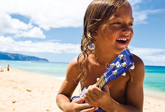 Young local boy playing the ukulele