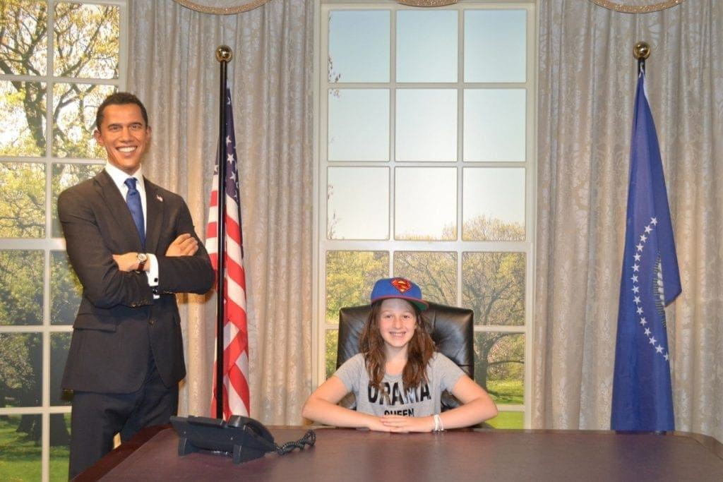 Girl sits down at desk beside wax figure of Barack Obama at Madame Tussauds