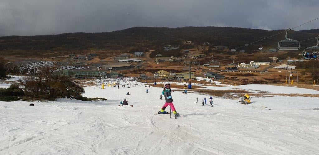 Young girl skis down hill at Perisher
