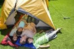 Family of four in a tent on back lawn