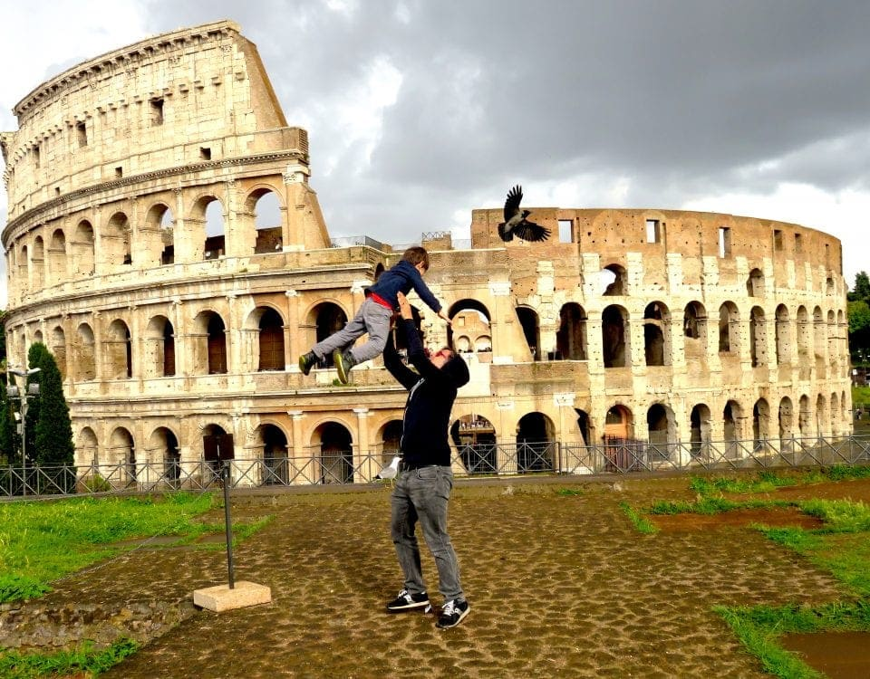 Father throws son up in the air in front of Colosseum