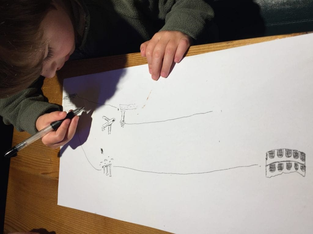 Small boy drawing a map of the city