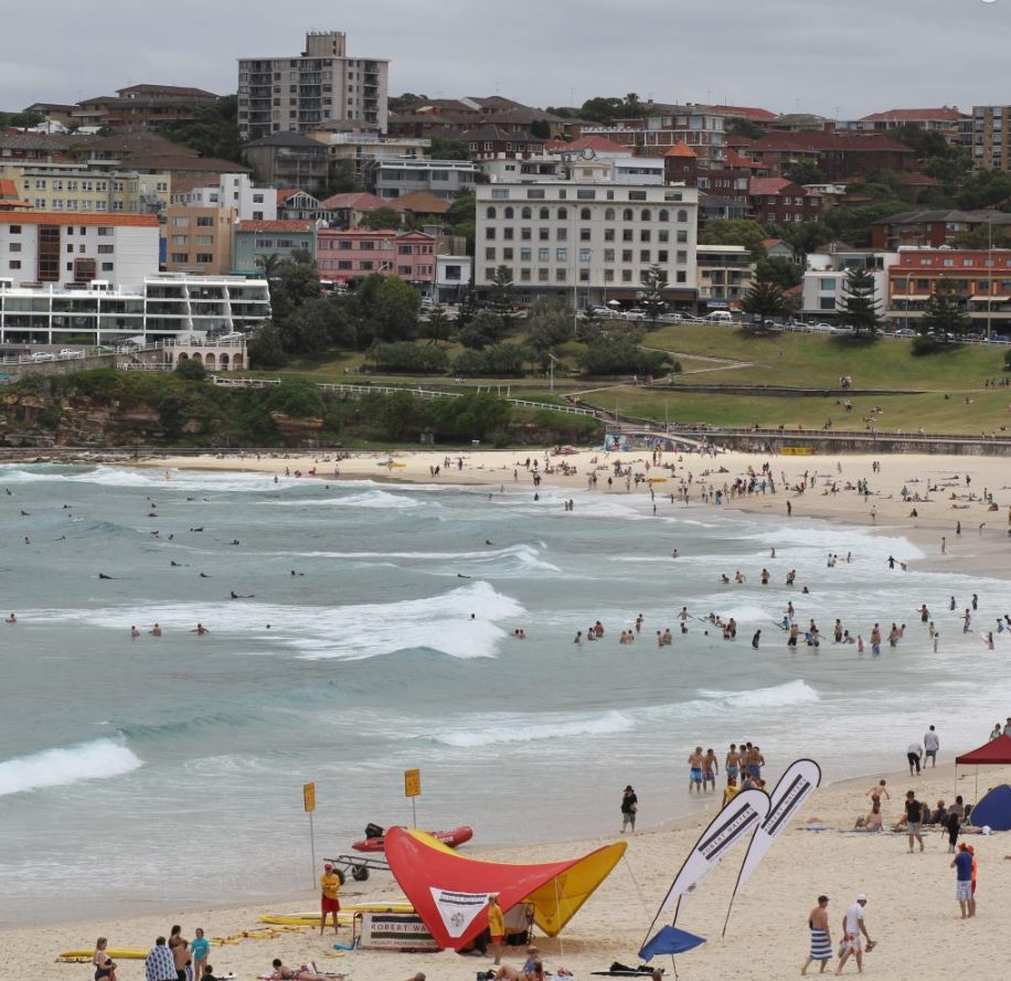 View of crowds and lifesaving flags at Bondi beach