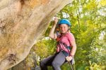 Young smiling girl in helmet abseils rock