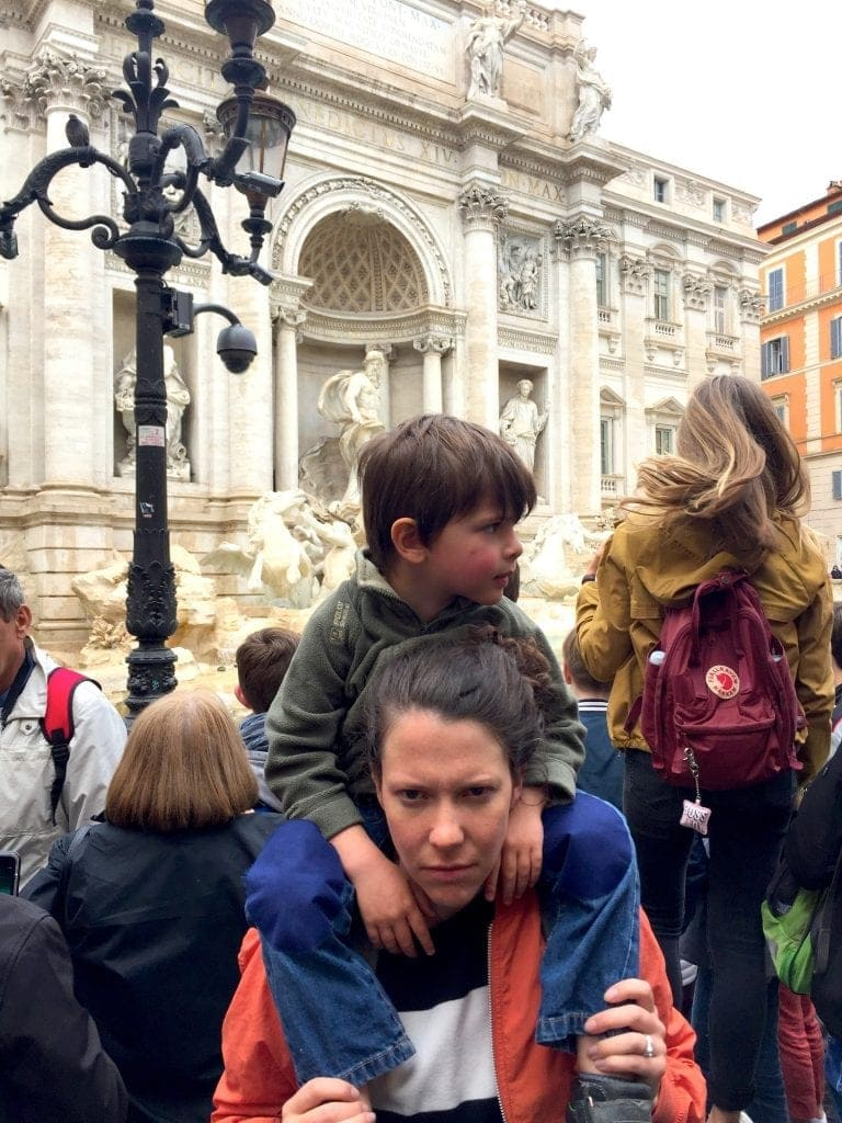Woman frowns with boy sitting on her shoulders in front of Trevi fountain