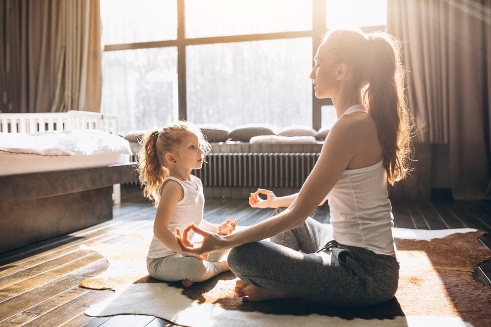 Mum and daughter sitting, meditating, practicing mindfulness