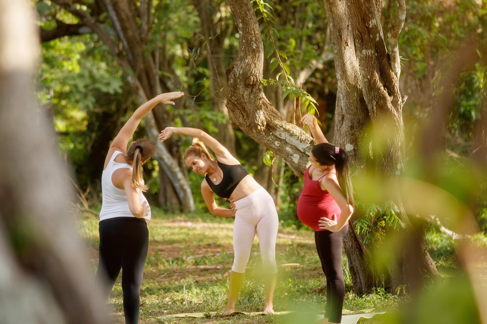 3 women stretching in park