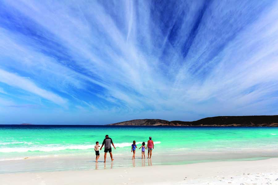 a family on the beach at hellfire bay in western australia. image tourism australia