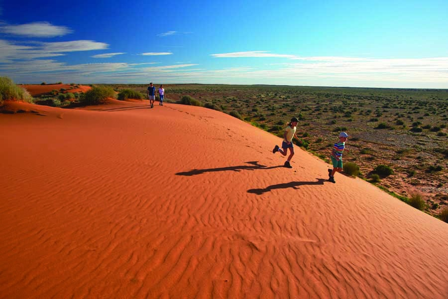 children running on sand dunes near william creek. image south australian tourism commission