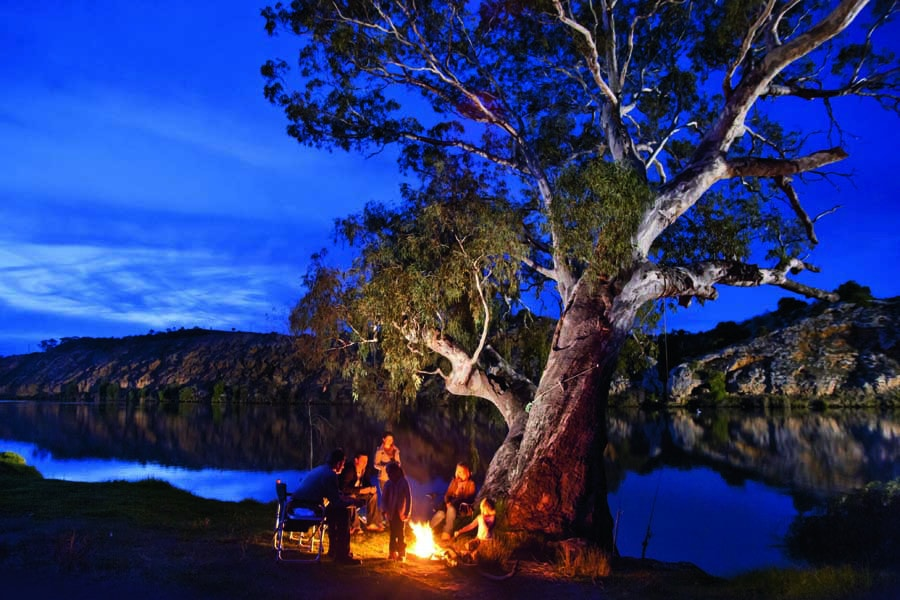 a family sitting around the campfire on the murray river in south australia. image south australia tourism commission 1