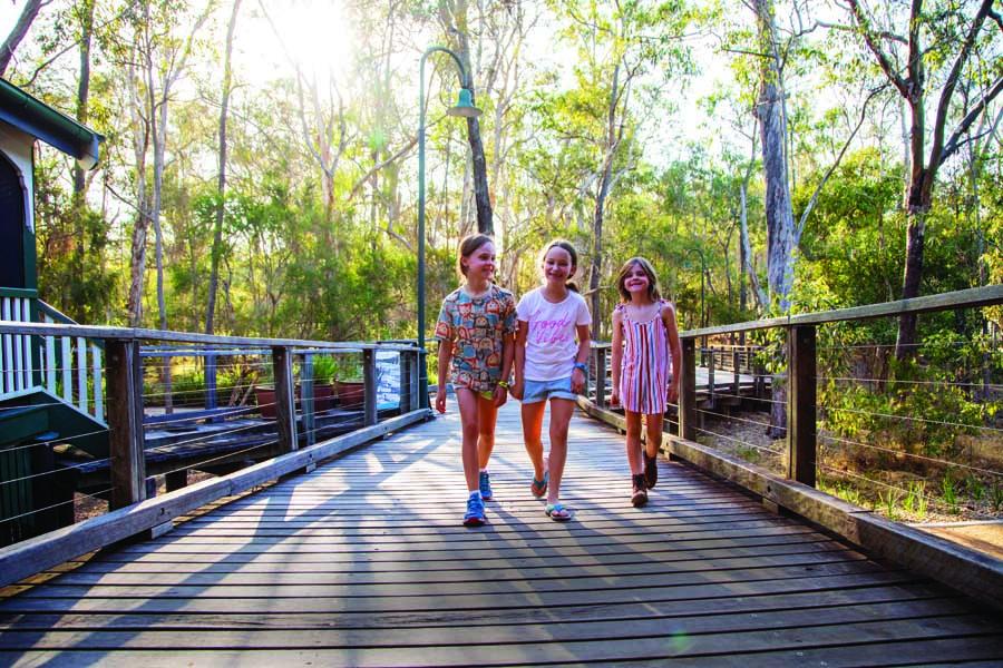 children on the boardwalk at boondall wetlands environment centre