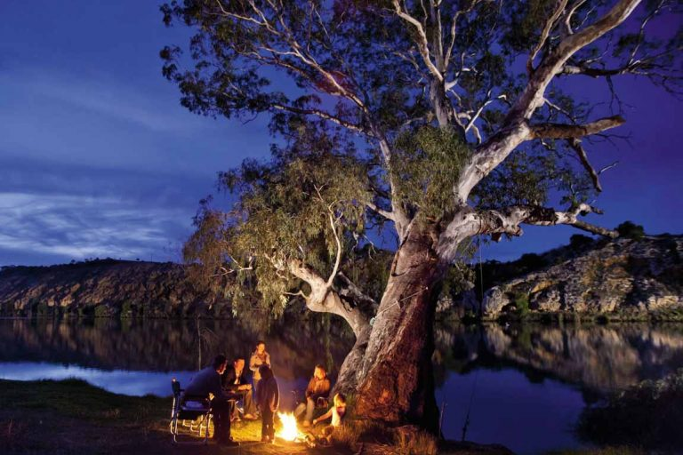 feature a family sitting around the campfire on the murray river in south australia. image south australia tourism commission 1