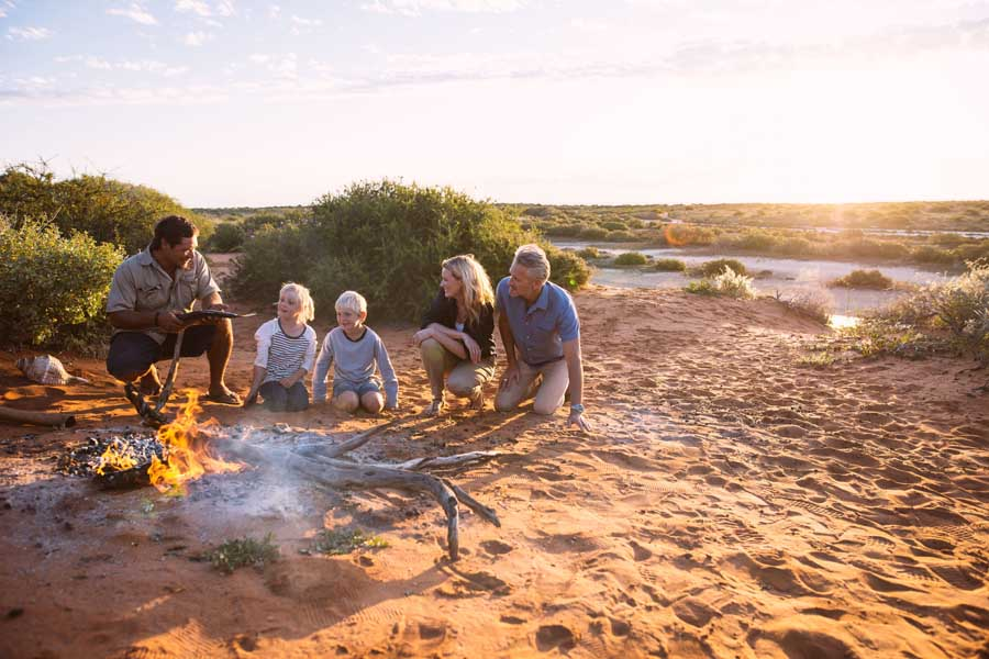 a family around a campfire on an indigenous tour at monkey mia. - travel with kids