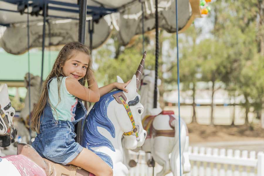 a girl riding the merry go round at crowne plaza hunter valley