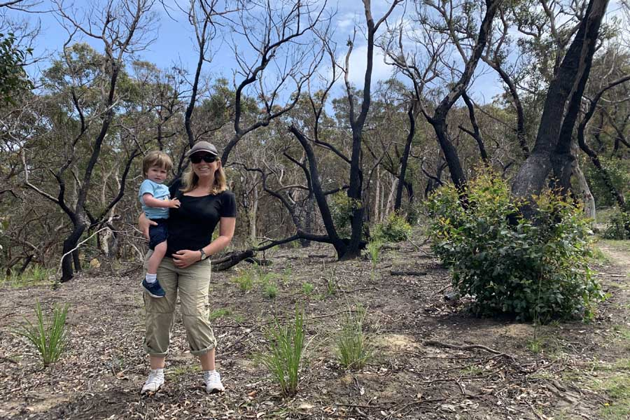 angela and oliver among the charred trees at durras