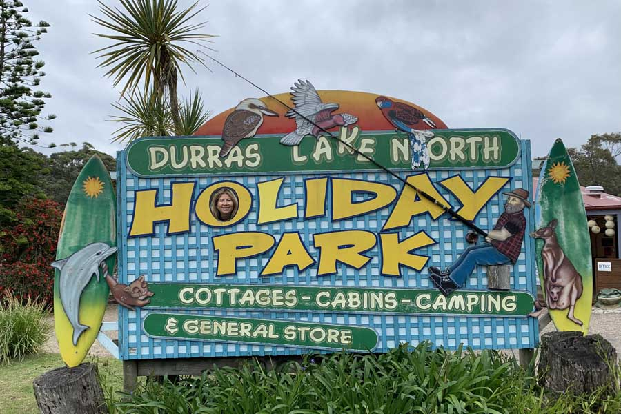 angela posing in the sign welcoming guests to durras lake north holiday park