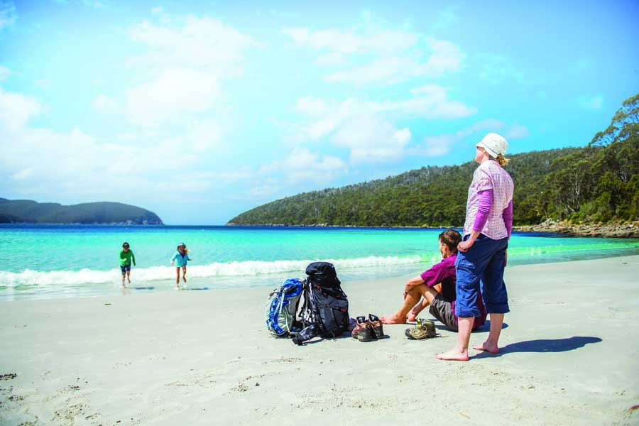 a family taking a break at fortescue bay while hiking the three capes track. image tasmania parks and wildlife service