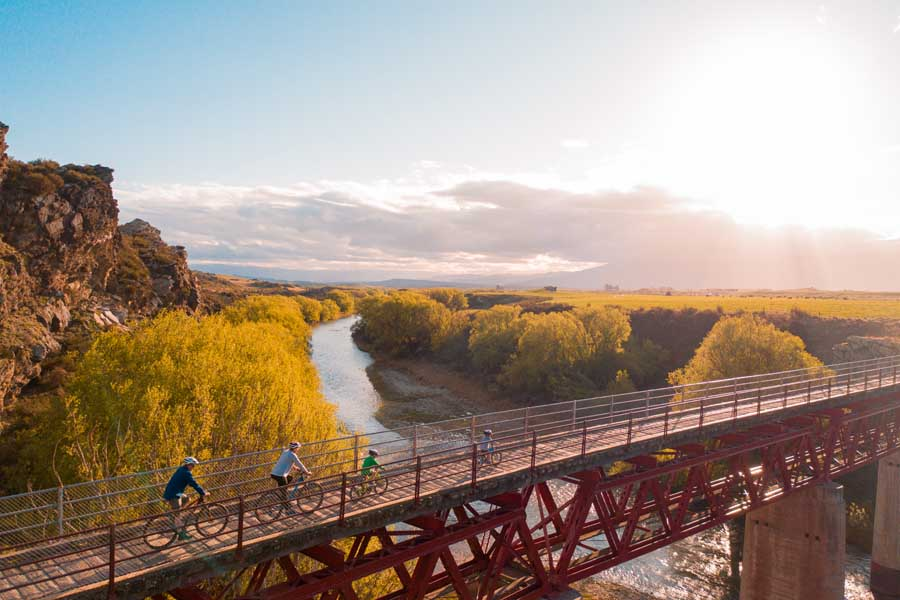 a family cycling the central otago rail trail in new zealand. image tourism central otago hayden parsons