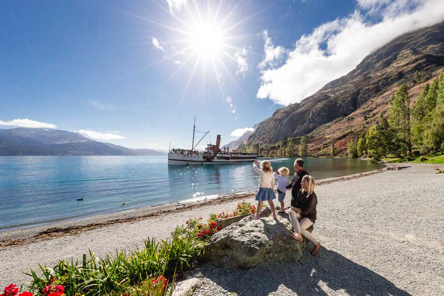 a family waving at the tss earnslaw in queenstown, new zealand