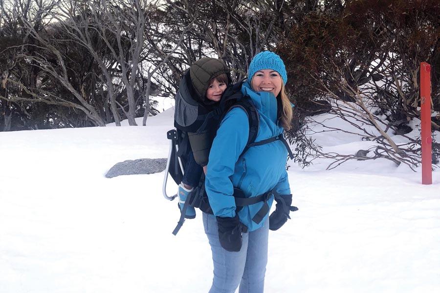 angela piggybacking oliver to dinner in the panda child carrier in Perisher ski resort