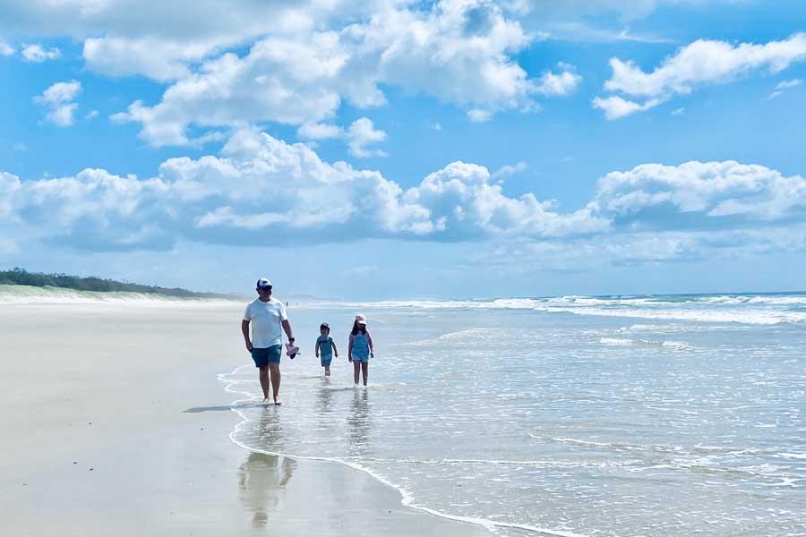 family walks along peregian beach
