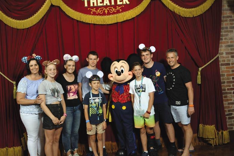 rebecca mason and her family with talking mickey at magic kingdom disneyworld in 2018