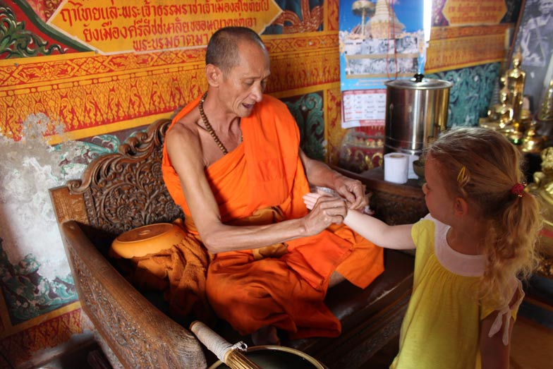 Beatrice receiving a blessing from a monk, Thailand Travel with five year old