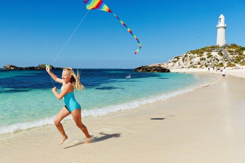 A girl flying a kite on Pinky Beach on Rottnest Island. Image Rottnest Island Authority