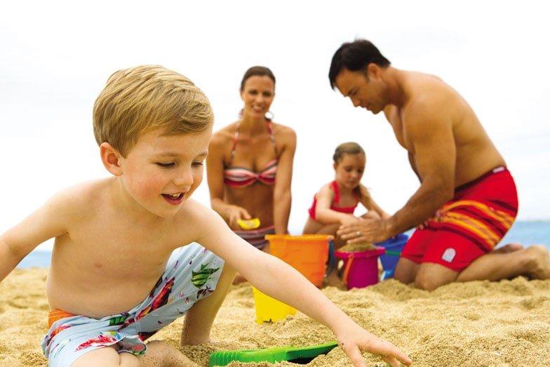 A family playing in the sand at Hilton Hawaiian Village Waikiki Beach Resort